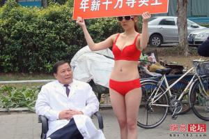 นักจิตวิทยาชาวจีน จ้างนางแบบสาวเซ็กซี่ ชูป้ายโปรโมตตัวเอง